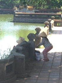 Some complex workers taking a break by the pond